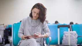 La mujer está comprobando datos en su pasaporte y en un boleto en el aeroplano en un pasillo que espera del aeroport, registrándo almacen de metraje de vídeo