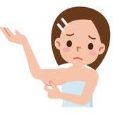 La mujer está comprobando su tríceps y parece unpleased Fotos de archivo