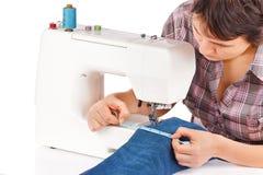 La mujer está cosiendo en la máquina de coser foto de archivo