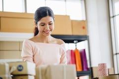 La mujer está dando la caja del paquete de las compras en línea, servicio a domicilio fotografía de archivo libre de regalías
