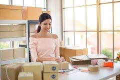 La mujer está dando la caja del paquete de las compras en línea, servicio a domicilio imagenes de archivo