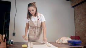 La mujer está desenrollando la arcilla en la tabla usando el rodillo en estudio de la cerámica almacen de metraje de vídeo