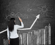La mujer está dibujando el organigrama de rascacielos en el tablero de tiza negro Fotos de archivo libres de regalías