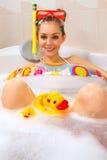 La mujer está disfrutando de un baño en máscara con el tubo respirador. Fotografía de archivo