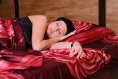 La mujer está durmiendo en la cama Imagenes de archivo