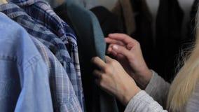 La mujer está eligiendo la ropa de los hombres en la tienda, cámara lenta almacen de video