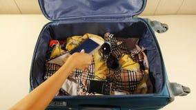 La mujer está embalando la maleta del equipaje, poniendo el traje de baño, la cámara, el pasaporte y un paquete de dólares de EE. metrajes