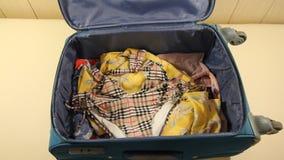 La mujer está embalando la maleta del equipaje, poniendo el traje de baño, la cámara, los vidrios, el pasaporte y mucho efectivo  almacen de metraje de vídeo