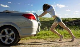 La mujer está empujando el coche roto Foto de archivo libre de regalías