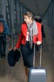 La mujer está en el movimiento con una maleta Imagenes de archivo