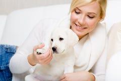 La mujer está en el sofá con el perrito blanco Fotos de archivo