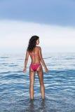 La mujer está entrando una agua de mar Foto de archivo libre de regalías