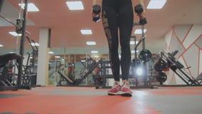 La mujer está entrenando con pesas de gimnasia en el gimnasio almacen de metraje de vídeo