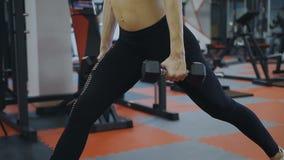 La mujer está entrenando con pesas de gimnasia en el gimnasio almacen de video
