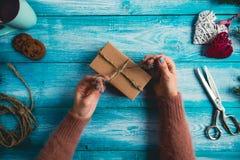 La mujer está envolviendo regalos de Navidad Foto de archivo