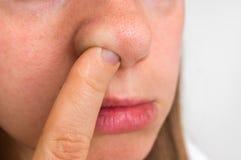 La mujer está escogiendo su nariz con el finger dentro Fotos de archivo libres de regalías