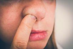 La mujer está escogiendo su nariz con el interior del finger - estilo retro Imagen de archivo
