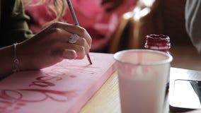 La mujer está escribiendo con la pintura en el tablero de madera, sentándose dentro metrajes