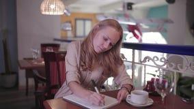 La mujer está escribiendo en un cuaderno que se sienta en un restaurante almacen de metraje de vídeo