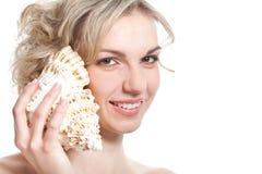 La mujer está escuchando el sea-shell Imagen de archivo
