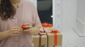 La mujer está girando en brazos una decoración roja del árbol de navidad en la forma de bola almacen de metraje de vídeo