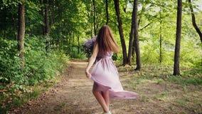 La mujer está gozando del olor de la lila almacen de metraje de vídeo