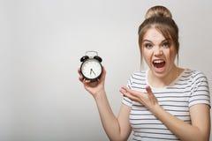 La mujer está gritando Mujer que sostiene un despertador imagenes de archivo