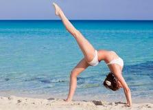 La mujer está haciendo ejercicio de la flexibilidad en la playa Foto de archivo