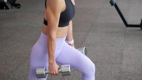 La mujer está haciendo las estocadas para las piernas con pesas de gimnasia en sus manos en gimnasio almacen de metraje de vídeo