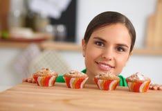 La mujer está haciendo las tortas en la cocina Fotos de archivo