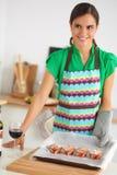 La mujer está haciendo las tortas en la cocina Imágenes de archivo libres de regalías