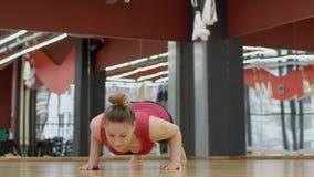 La mujer está haciendo un tablón del ejercicio con una desviación detrás en clase de la yoga almacen de metraje de vídeo