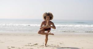 La mujer está haciendo yoga en la playa almacen de metraje de vídeo