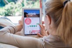 La mujer está instalando el uso de Airbnb en la tableta de Lenovo Imágenes de archivo libres de regalías