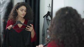 La mujer está intentando los vestidos en vestuario en tienda y está tomando el selfie por el móvil almacen de metraje de vídeo