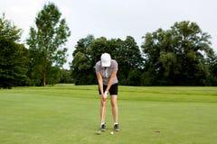 La mujer está jugando a golf el verano del curso foto de archivo