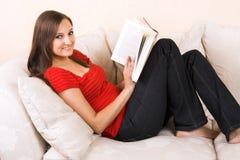 La mujer está leyendo en un salón fotos de archivo
