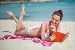 La mujer está leyendo un libro en una playa Fotos de archivo libres de regalías