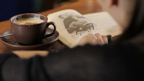 La mujer está leyendo un libro y un café de consumición Tirado de detrás metrajes