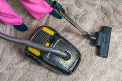 La mujer está limpiando la alfombra con la aspiradora con el aspirador imagenes de archivo