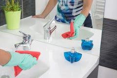 La mujer está limpiando un cuarto de baño Imágenes de archivo libres de regalías