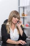 La mujer está llamando por teléfono en el contador de la recepción Imagen de archivo libre de regalías