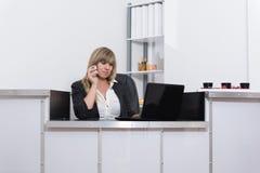 La mujer está llamando por teléfono en el contador de la recepción Fotografía de archivo libre de regalías