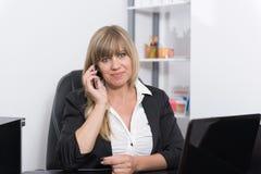 La mujer está llamando por teléfono en el contador de la recepción Imagenes de archivo