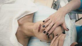 La mujer está llevando a cabo un tratamiento del balneario a una muchacha atractiva joven almacen de metraje de vídeo