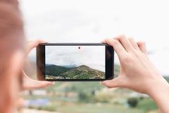 La mujer está memorizando un vídeo en su teléfono Los conceptos de la tecnología hacen vida más fácil dondequiera que usted sea Fotografía de archivo libre de regalías