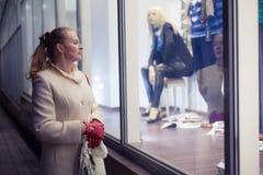 La mujer está mirando el escaparate Foto de archivo libre de regalías