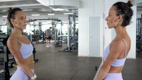 La mujer está mirando el espejo en su cuerpo hermoso juguetón después de entrenamiento en gimnasio almacen de metraje de vídeo