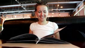 La mujer está mirando el menú en el restaurante, dando vuelta a las páginas almacen de video