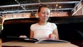 La mujer está mirando el menú en el restaurante, dando vuelta a las páginas almacen de metraje de vídeo